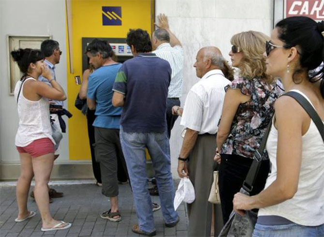 People line up to withdraw cash from an automated teller machine (ATM) outside a Piraeus Bank branch in Iraklio on the island of Crete, Greece.