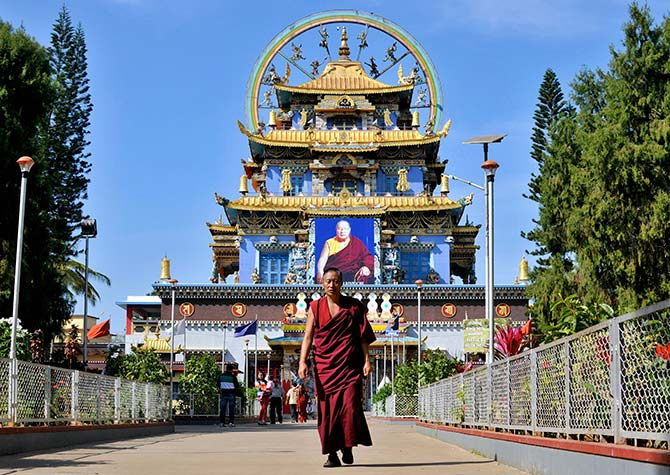 A Tibetan Buddhist monk walks in front of the Golden Temple inside the Nyingmapa Monastery in Bylakuppe, southwest of Bengaluru, previously known as Bengaluru