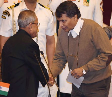 Image: President Pranab Mukherjee shakes hands with the new Cabinet minister Suresh Prabhu after administering him oath of office. Photograph: PTI photo