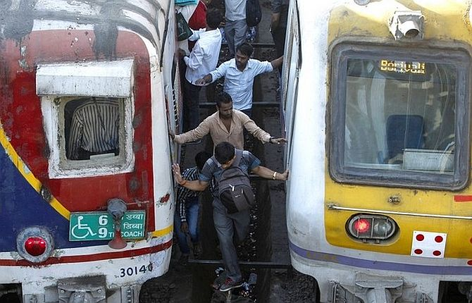 Commuters try cross railway tracks as trains wait at a suburban station in Mumbai.