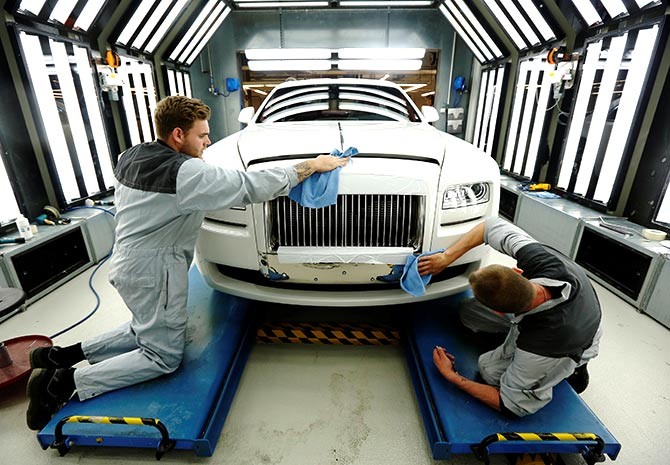 Employees Joe Don (L) and Darren Lowarson give a Rolls Royce Ghost its final finish polish at the Rolls Royce Motor Cars factory at Goodwood near Chichester in southern England