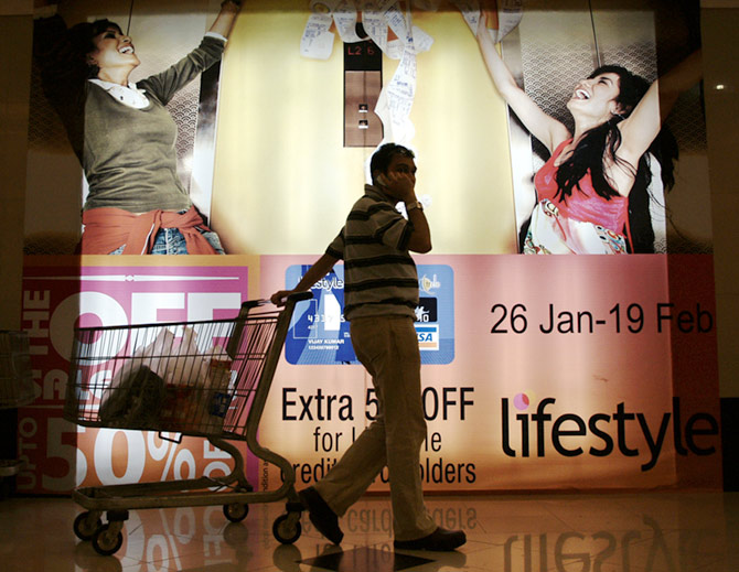 An Indian consumer pulls his trolley as he passes by an advertising display at a shopping mall.