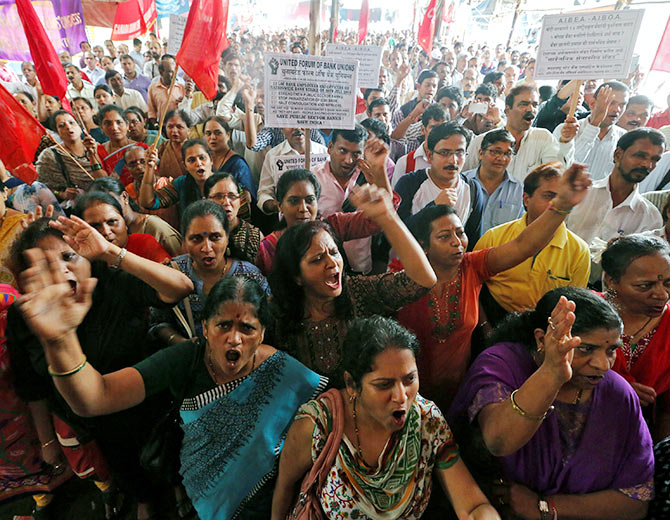 IMAGE: Bank employees shout slogans as they attend a strike opposing the government's proposal to merge State Bank of India's associate banks with SBI, and against the government's proposed move to privatise IDBI Bank.