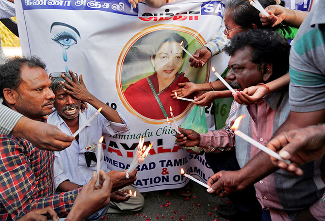 Supporters of Tamil Nadu Chief Minister Jayalalithaa mourn in front of a banner bearing her photograph during a procession in Ahmedabad, on December 6, 2016.
