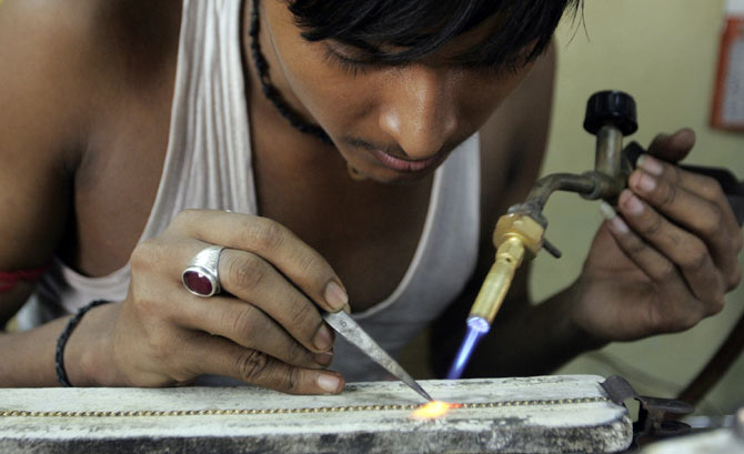 A goldsmith makes ornaments in a workshop in Ahmedabad