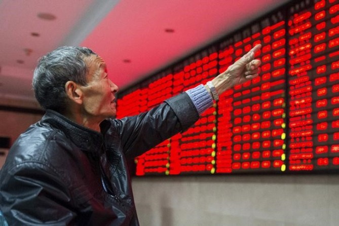 An investor points to an electronic board showing stock information as he speaks to another investor, at a brokerage house in Nanjing, Jiangsu province, China, November 19, 2015. REUTERS/China Daily/Files