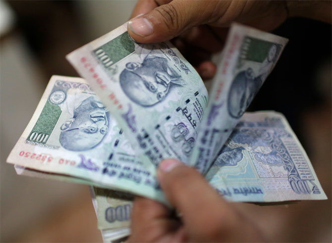 Rupee climbs to 2-week high against dollar, up 11 paise