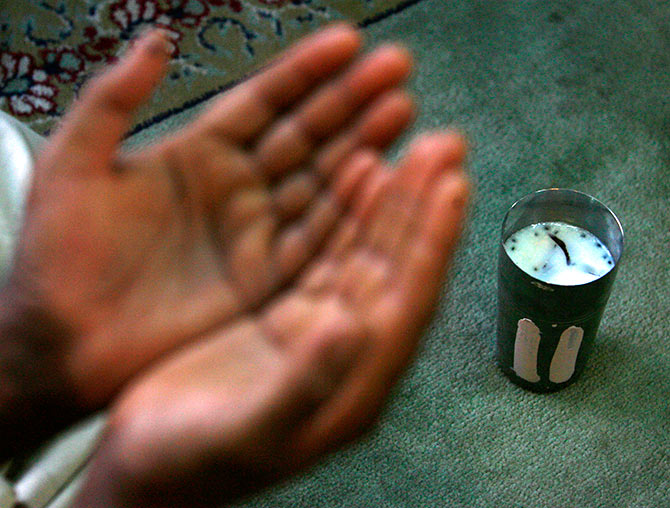 A Kashmiri Muslim man prays in front of a glass of traditional drink called Sharbat, made of a mixture of milk, almond and coconut before breaking his day-long fast during Ramadan inside the shrine of a Sufi saint in Srinagar August 24, 2009. Muslims around the world abstain from eating, drinking and sexual relations from sunrise to sunset during Ramadan, the holiest month in the Islamic calendar. Fayaz Kabli/REUTERS