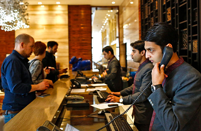 Receptionists attend to guests at the Crown Plaza hotel, run by the InterContinental Hotels Group, New Delhi, January 31, 2014. Photo: Anindito Mukherjee/Reuters