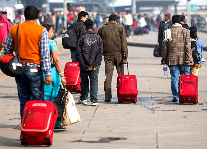 ommuters carry their luggage outside a railway station during a strike in New Delhi February 20, 2013. Photo: Adnan Abidi/Reuters