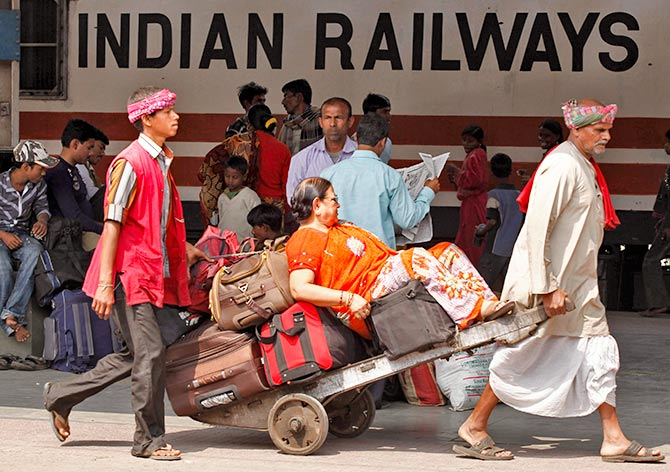 Porters transport a passenger and her luggage on a hand-pulled cart at a railway station in Kolkata February 25, 2011. Photo: Rupak De Chowdhuri/Reuters