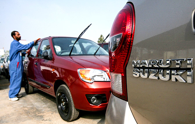 A worker cleans a parked car at the Maruti Suzuki's stockyard on the outskirts of Jammu January 4, 2011. Photo: Mukesh Gupta/Reuters