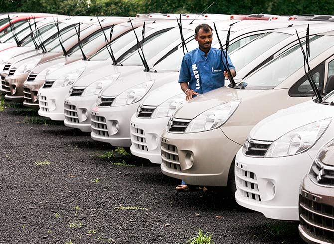 An employee works beside parked cars at the Maruti Suzuki's stockyard on the outskirts of the western Indian city of Ahmedabad July 24, 2010. Photo: Amit Dave/Reuters