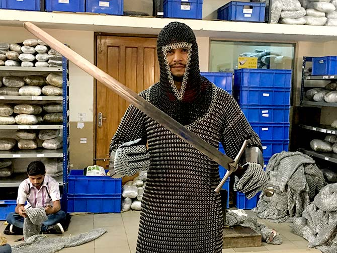 A worker poses with chain mail