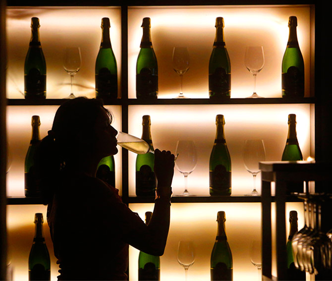 A woman poses with a glass of wine at a tapas bar in Mumbai March 9, 2013. Picture taken March 9, 2013. Photo: Vivek Prakash/Reuters
