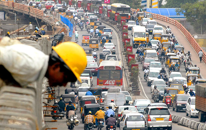 A worker leans on the wall of a flyover as traffic comes to a standstill on a busy road in the southern Indian city of Hyderabad June 27, 2007. Photo: Krishnendu Halder/Reuters
