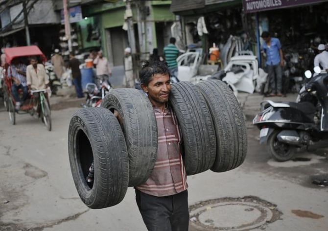 Image: A worker carries car tyres for rethreading at an automobile spare parts market in the old quarters of Delhi. Photograph: Anindito Mukherjee/Reuters
