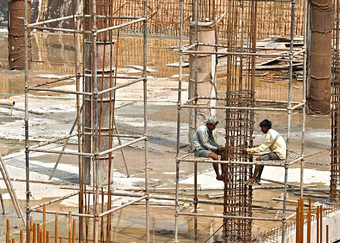 Labourers work at the construction site of a multi-level parking in Chandigarh July 10, 2014. Photo: Ajay Verma/Reuters