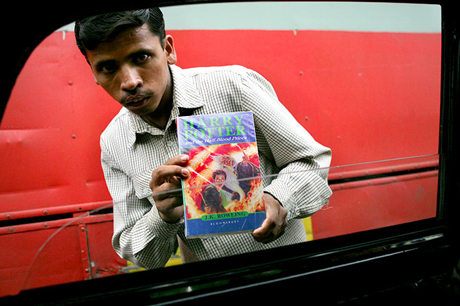"An Indian street hawker sells a pirated copy of the book ""Harry Potter and Half-Blood Prince"" for 250 rupees ($6), at a busy traffic intersection in Bombay, August 3, 2005. Photograph: Arko Datta/Reuters"