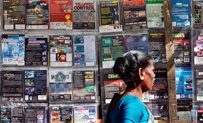 A woman walks past pirated DVDs and software on sale at a street side hawker shop in Mumbai November 12, 2009. Photo: Arko Datta/Reuters