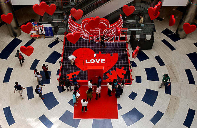 People arrange tiles of a heart-shaped puzzle during an event to promote Valentine's Day celebrations, inside a mall in Bengaluru. Photograph: Abhishek N Chinnappa/Reuters