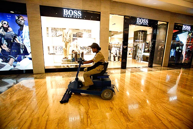An employee operates a floor cleaning machine in a Mumbai mall. Photograph: Vivek Prakash/Reuters