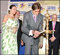 Lara Dutta looks on as Amitabh Bachchan lights the inaugural lamp at FICCI Frames 2005