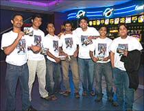 Fans wearing t-shirts featuring the star, pose for photographs