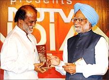 Rajnikanth receives the NDTV Indian award from Prime Minister Manmohan Singh