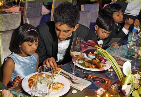 Dev Patel (second left) shows Rubina Ali (left) how to eat pizza at the Governors Ball