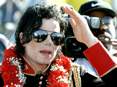 Michael Jackson shields his eyes from the sun as he arrives at Johannesburg International airport