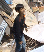 Azhar next to the debris of his home