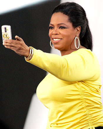 Oprah takes a picture of the crowd with her cell phone during a taping of the 24th season