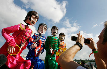 A man photographs giant puppets of Beatles on his mobile phone at Glastonbury Festival in Somerset
