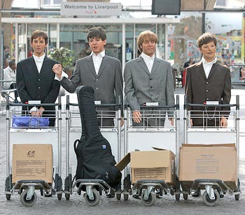 Four wax statues of Beatles pose with luggage trolleys after arriving in Liverpool