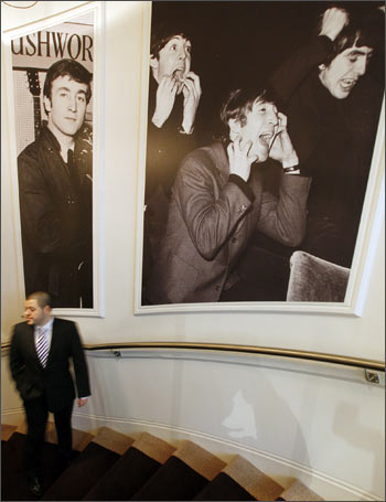 A man passes pictures of the Beatles on the main staircase at the Hard Days Night Hotel in Liverpool