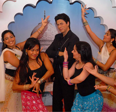 Bollywood Axion Dance Troupe perform around the wax figure of Shah Rukh Khan