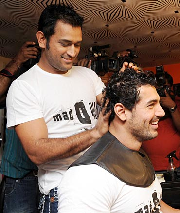 Mahendra Singh Dhoni plays with John Abraham's hair during a promotional event at Sapna Malhotra's Mad-O-Wat salon in Mumbai, December 2010.