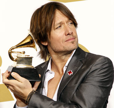 Keith Urban holds his award backstage