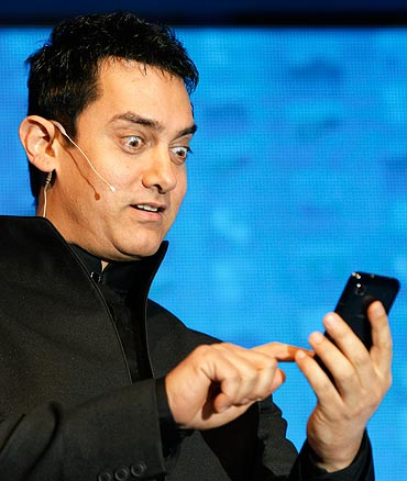 ... in New Delhi, Aamir Khan reacts as he holds a mobile phone