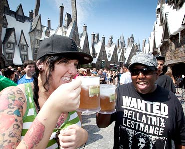 Visitors drink butterbeer during the grand opening