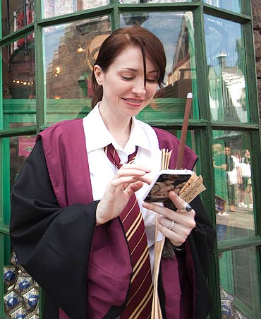 A guest, in her Hogwarts school regalia, uses a mobile phone