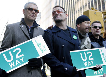 Adam Clayton, Bono, Edge and Larry Mullen hold street signs
