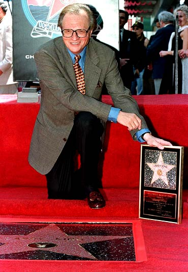 Larry King poses with his plaque after his star on the Hollywood Walk of Fame in 1997