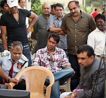 Sanjay Mishra, Ajay Devgn and Paresh Rawal watch the monitor while Ashwini Dhir (standing, second from right), looks on