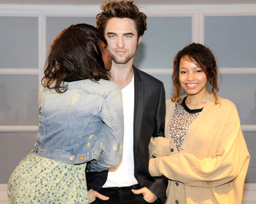 Visitors pose with a wax figure of Robert Pattinson