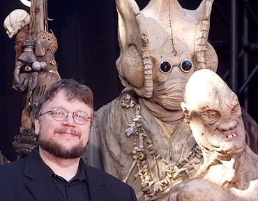Guillermo del Toro poses for photographers surrounded by characters from the movie Hel