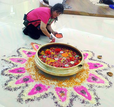 Housemates decorate the house with a rangoli