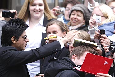 Shah Rukh Khan signs autographs after a news conference promoting his movie Don-2 in Berlin.