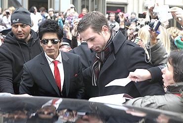 Shah Rukh Khan is helped to his car after leaving a news conference.
